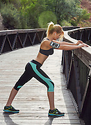 Female jogger stretching and warming up on trail in southern utah. Backlight, early morning light. Fitness image for lifestyle portfolio of Carole Jones Commercial Photography