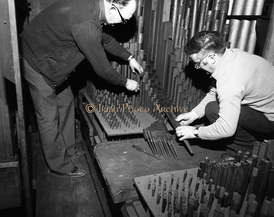 Pipe Organ Dismantling at Aungier Street.  (K86).1977..01.02.1977..02.01.1977..1st February 1977..A pipe organ built around 100 years ago for St Peter's Church (Church of Ireland),at Whitefriar / Aungier Street was being dismantled by Mr Gerry Smith and Mr Sam Wright of Dublin Organ Works. The organ was being dismantled for transfer to St Michael's Church,(Roman Catholic),in Blackrock,Co Cork.Image shows the dismanling of the wooden pipes by Mr Gerry Smith (right) and Mr Sam Wright.