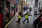 Two schoolchildren wearing hi-vis tabards dash across the pavement after alighting from a bus during a school trip to the West End, on 22nd November 2017, in London England.