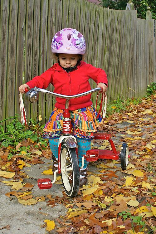 2-Year-Old Rides Tricycle on Sidewalk in Fall, Wears Helmet