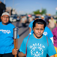 052714       Cable Hoover<br /> <br /> Special Olympics athlete Allen Leal takes his turn carrying the torch during the torch run in Gallup Tuesday.