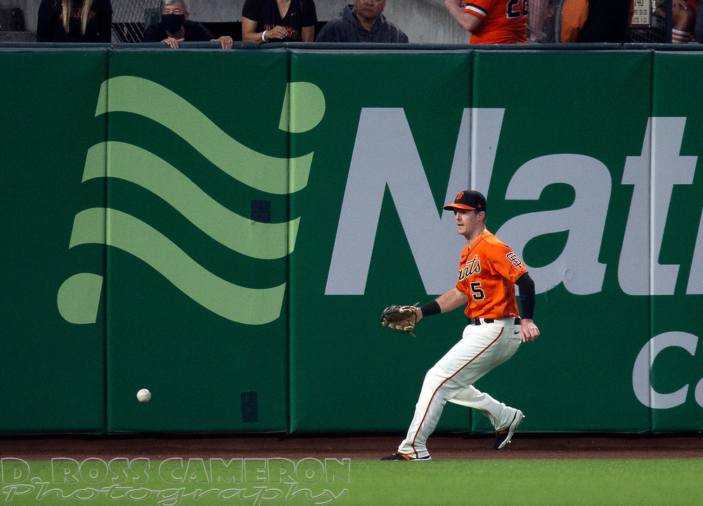 Oct 1, 2021; San Francisco, California, USA; San Francisco Giants center fielder Mike Yastrzemski (5) runs down a double off the bat of San Diego Padres center fielder Trent Grisham during the first inning at Oracle Park. Mandatory Credit: D. Ross Cameron-USA TODAY Sports
