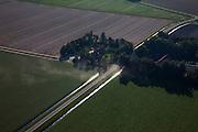 Nederland, Flevoland, Noordoostpolder, 08-09-2009. Planmatig aangelegde boerderij, stammend uit de tijd dat de polder in cultuur gebracht moet worden (vandaar cultuurboerderij of cultuurbedrijf). Gebouwd door de Rijksdienst voor de IJsselmeerpolders met geprefabriceerde betonelementen. Windsingel rond de boerderij. .Systematically built farmhouse, dating from the time the polder still had  to be cultivated (hence agricultural farm or company culture). Built by the Department for the IJsselmeer polders with prefabricated concrete elements. Windbreaks around the farm.  .(toeslag); aerial photo (additional fee required); .foto Siebe Swart / photo Siebe Swart