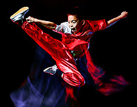 wushu chinese boxing kung fu Hung Gar fighter isolated child isolated on black background with speed light painting effect motion blur