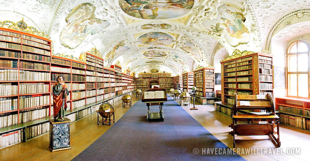 Interior of one of the main library rooms of the Strahov Library. Statue at left is of St. John the Evangelist. Book holder at right was specially designed for this library and keeps the books facing the reader as the wheel is turned.