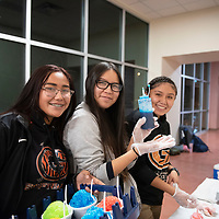 Madison Belone, left, Felisha Lee, center, and Jordan Yazzie, members of the Gallup Bengals softball team sell  snow cones to fundraise for the team Thursday, Jan 9 at the Gallup Bengals boys varsity basketball game at Gallup High School.