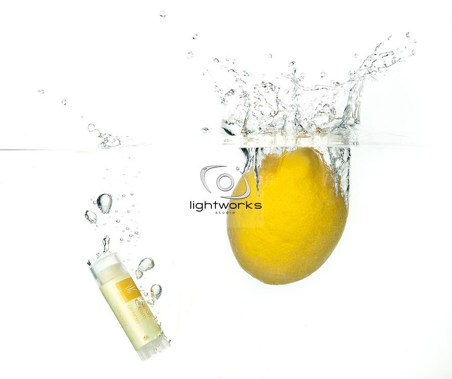 Product photograph of Soapcreek Lipbalm.<br /> Lemon Creme LipMend product splashing into water with a yellow lemon.