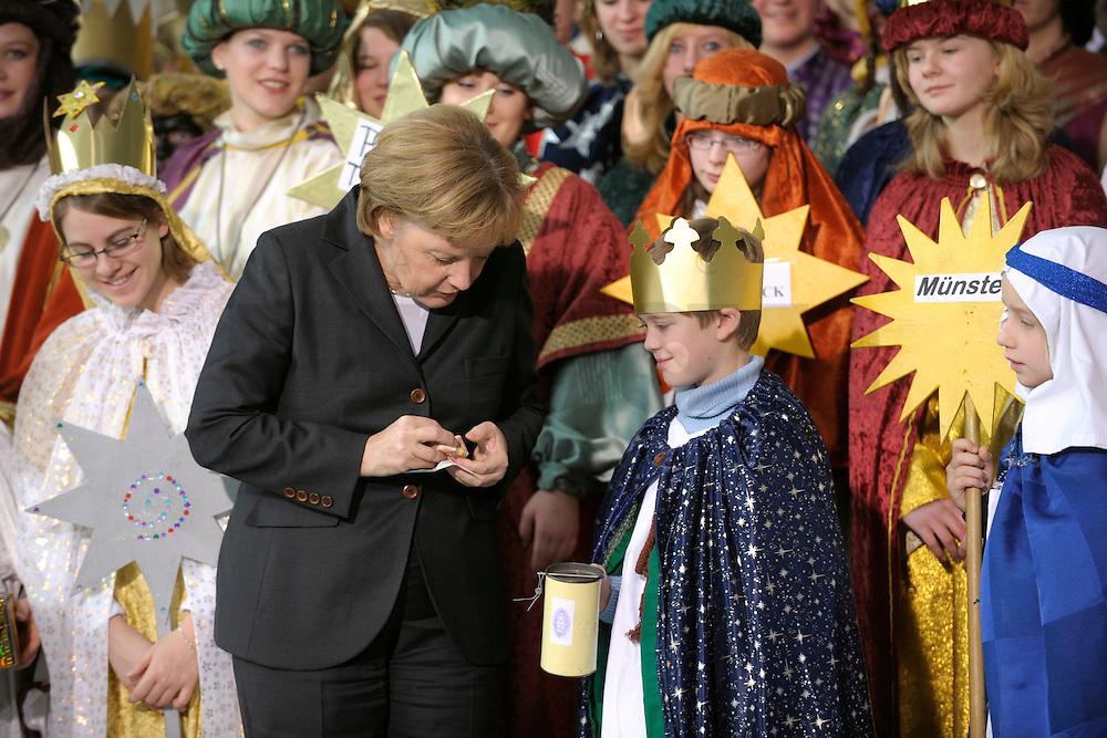 04 JUN 2008, BERLIN/GERMANY:<br /> Angela Merkel, CDU, Bundeskanzlerin, steckt ihre Spende in die Spendendose von einem der Heiligen drei Koenige, waehrend dem Empfang der Sternsinger im Bundeskanzleramt<br /> IMAGE: 20080104-01-022<br /> KEYWORDS: Heilige drei Koenige, Heilige drei Könige, spendet, Geld, Geldscheine, Kanzleramt