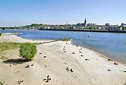Nederland, Nijmegen, 26-4-2020 Tijdens dit warme weekend was het voor veel mensen moeilijk thuis te blijven . Beeld van het waalstrandje op Veur-Lent. Er kon goed afstand gehouden worden tot elkaar .Foto: Flip Franssen