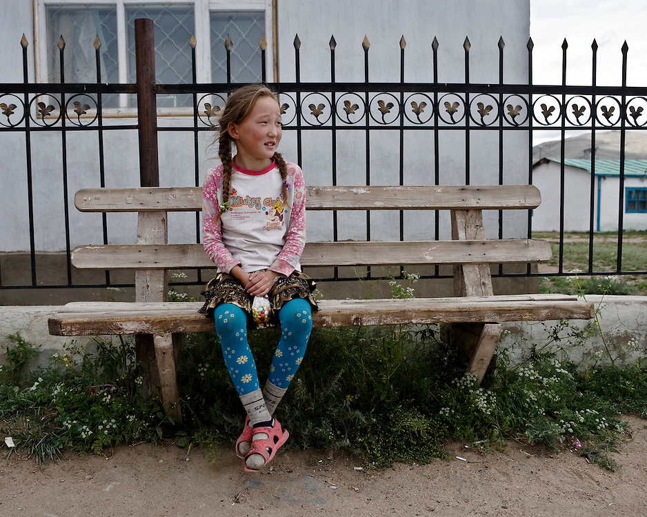 Portrait of a young Mongolian girl sitting on a bench