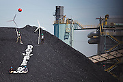 """Kate Clark (l-r),  Eric Ross, Erik Bonnett and Tom Weiss stage a protest with mock wind turbines and a giant """"Renewables Now"""" banner on the coal pile at the Valmont Power Plant in Boulder, Colorado on April 27, 2010. The four climate activists claimed the coal mound for over an hour before they were arrested for trespass."""