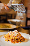 Parmesan cheese (parmigiano-reggiano) is grated over tajarin al ragu (pasta with meat sauce) at an Italian restaurant in La Morra, Italy.