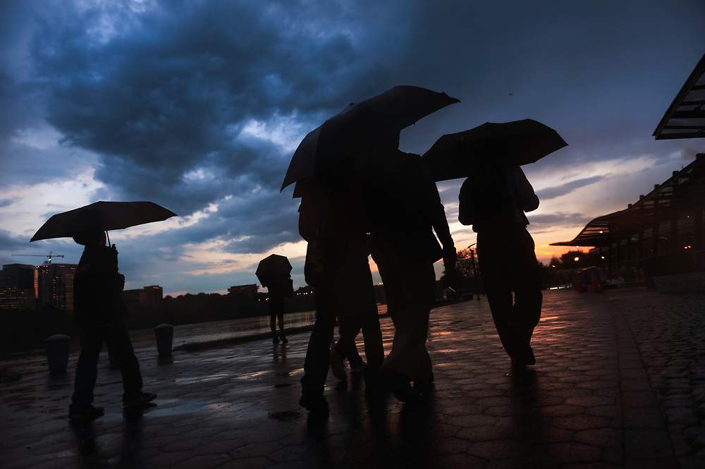 The sun breaks through the clouds as it sets on the horizon after a bout of stormy weather, casting a group of walkers in shadow along the Georgetown Waterfront. Washington, D.C.