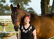 A young woman poses with her horse in the early evening light at White Fences Equestrian Center in Manor, TX.
