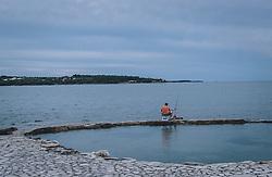THEMENBILD - ein Fischer fischt mit seiner Angel am Ufer, aufgenommen am 03. Juli 2020 in Novigrad, Kroatien // a fisherman fishes with his rod on the shore, in Novigrad, Croatia on 2020/07/03. EXPA Pictures © 2020, PhotoCredit: EXPA/ Stefanie Oberhauser