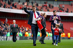 Arsenal's Aaron Ramsey salutes the fans with his family on the pitch after the final whistle of the Premier League match at the Emirates Stadium, London.