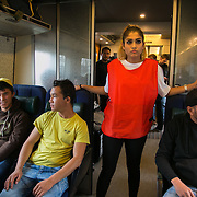 A Swedish volunteer and Afghan refugees on their way on a train to Sweden and safety.  An unprecedented number of refugees arrived from Germany in early September, most being Syrian war refugees, some from Afghanistan. Most wanted to travel on to Sweden and a number of Danish citizens created a spontanious network to assist the refugees with travel, food, clothes and psycological support.