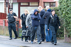 © Licensed to London News Pictures. 27/09/2012. Salford , UK . People are led away from the property by police.  Police at the scene of a house on 5 Acresfield Road , Salford , where bullets were fired in to the front porch window . Photo credit : Joel Goodman/LNP