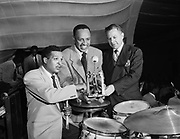 """Ackroyd 01634-2. """"Norm Easley. Drum pedal at McElroy's"""" (Lionel Hampton with new 'Ghost' bass drum  pedal at McElroy's ballroom. The Ghost was designed by J.R. """"Bob"""" Ramsey of Springfield Oregon. The patent was applied for on October 27, 1947, and was granted on May 8, 1951. Norman L. Easley, the inventor's attorney, is delivering the pedal to Hampton's drummer, who is probably Art Young. The Ghost drum pedal was later manufactured by Ludwig, who bought the rights to it in 1975. They discontinued it in 1981, due to maintenance problems and an industrial accident involving the pedal's springs at their plant. Photo taken July 21, 1949. This date was confirmed by the Oregonian newspaper of this date, the Hampton band had played the previous Friday July 15, and were booked on short notice for a return engagement.) McElroy's was at 424 SW Main, and was demolished in 1980 to make room for the Portland building."""