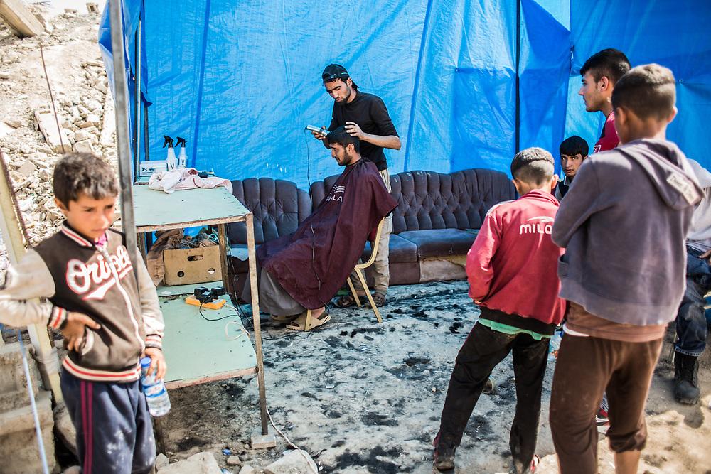 A man gets hair cut in a refugee camp near West Mosul.