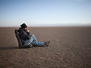 A man takes a break in a chair in the Gobi desert while his jeep is being repaired.<br /> Road trip with a Jeep in the Gobi region.