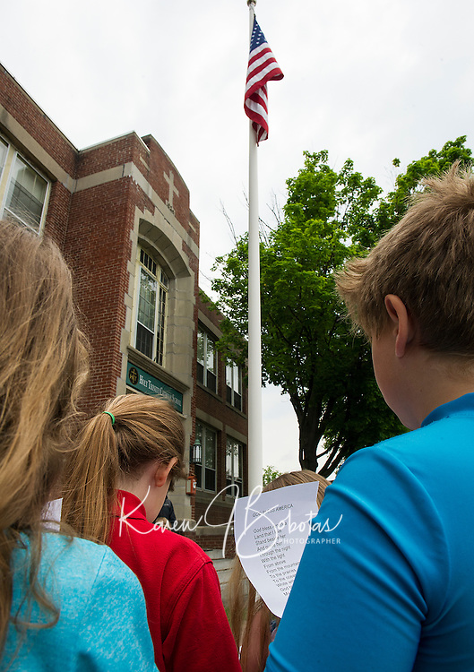 Holy Trinity Catholic School students join together to sing God Bless America to conclude their Memorial Day Service on the front lawn Friday morning.  (Karen Bobotas/for the Laconia Daily Sun)
