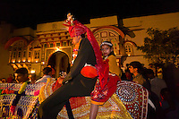 Bride groom on horseback during a night time wedding procession in the village of Rohet, Rajasthan, India