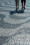 Shadows of a man and woman across paviers forming wavy lines and geometric patterns in Rossio Square in the City of Lisbon, Portugal