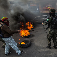 Protestors face off with soldiers in Comayagüela at a burning barricade of tyres as the soldiers prepare to remove the tyres from the road. The protestor in the foreground is covered in soot from the fires.