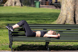 © Licensed to London News Pictures. 05/04/2020. London, UK. A young relaxes on a bench in the warm weather. Members of the public come out to exercise In Hyde Park as temperatures reach over 21c this weekend. Hyde Park was busy with walkers, runners and cyclists as the Government urged the public not to leave home during the fine weather as the Coronavirus crisis continues. Photo credit: Alex Lentati/LNP