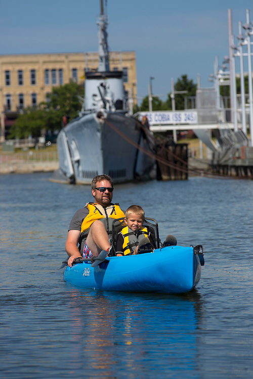 The Ludtke family peddle kayaks past the USS Cobia submarine at the maritime museum in Manitowoc, Wisconsin.  Photo by Mike Roemer