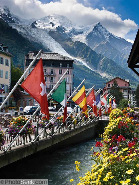 International flags fly over the River Arve in Chamonix, France, beneath Mont Blanc (4808 meters or 15,774 feet), the highest peak in Western Europe. Mont Blanc (Monte Bianco in Italian) was first climbed in 1786 by two men from Chamonix. Today Chamonix is an important world center for mountaineering.