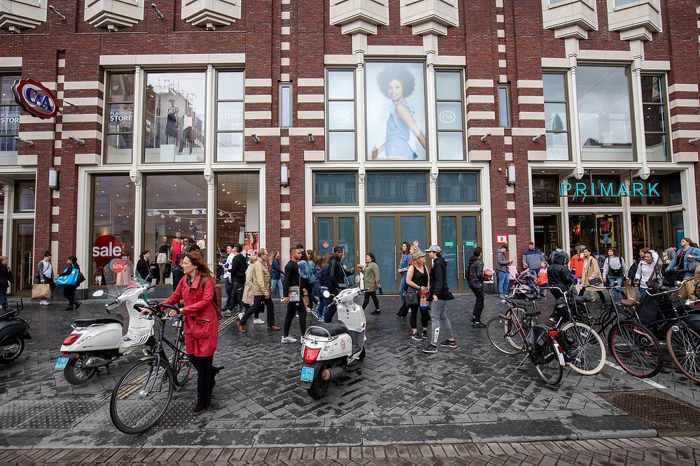 De winkels van C&A en Primark aan het Damrak in Amsterdam. Vooral Primark staat onder druk om de omstandigheden waar de kleren worden gemaakt te verbeteren.<br /> <br /> Shops of C&A and Primark at the Damrak in Amsterdam. Especially Primark is known for bad labour conditions for the workers in the garment industry.