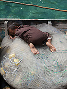 Kid sleeping on a fish net. Fishermen fishing with nets on duggout canoe off Boheydulang island.
