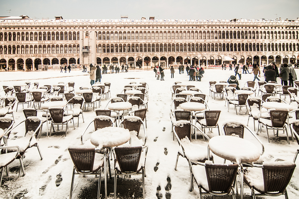 """VENICE, ITALY - 28th FEBRUARY/01st MARCH 2018<br /> Snow-covered tables and chairs on St. Mark Square in Venice, Italy. A blast of freezing weather called the """"Beast from the East"""" has gripped most of Europe in the middle of winter of 2018, and in Venice A snowfall has covered the city with white, making it fascinating and poetic for citizen and tourists.   © Simone Padovani / Awakening"""