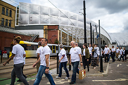 © Licensed to London News Pictures . FILE PICTURE DATED 26/06/2017 of fire fighters and staff from Manchester Central Fire Station , wearing symbolic Manchester bee t-shirts , passing Victoria station during a walk from Manchester Central Fire Station to St Ann's Square in Manchester City Centre for a short ceremony and release of 22 doves , in commemoration of the 22 people killed in a murderous terrorist attack , carried out by Salman Abedi , following an Arina Grande concert at the Manchester Arena , on 22nd May 2017 . Local fire crews have expressed frustration , laid bare in the Kerslake Review published today (27th March 2018) after they were held back from attending to support other emergency services for nearly two hours after the bombing , on the night of the attack . Photo credit : Joel Goodman/LNP