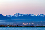 Boundary Bay, apartment buildings in Burnaby and peaks of Meslilloeet Mountain in the Coast Range.  Photographed from Boundary Bay Regional Park in Tsawwassen, British Columbia, Canada.
