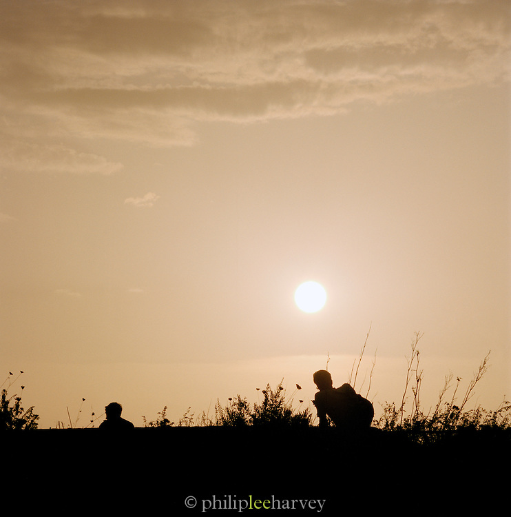 Couple watching sunset, Panarea, Aeolian Islands, Italy