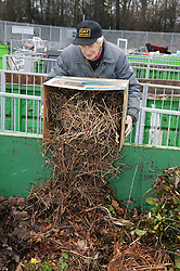 Man putting garden rubbish into the skip at the Tipsmart recycling centre at Calverton,