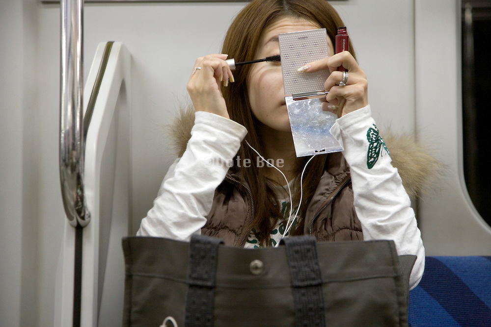 commuter puts on makeup Japan daily life