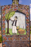 Tombstone showing a man picking pears in an orchard,  The  Merry Cemetery ( Cimitirul Vesel ),  Săpânţa, Maramares, Northern Transylvania, Romania.  The naive folk art style of the tombstones created by woodcarver  Stan Ioan Pătraş (1909 - 1977) who created in his lifetime over 700 colourfully painted wooden tombstones with small relief portrait carvings of the deceased or with scenes depicting them at work or play or surprisingly showing the violent accident that killed them. Each tombstone has an inscription about the person, sometimes a light hearted  limerick in Romanian. .<br /> <br /> Visit our ROMANIA HISTORIC PLACXES PHOTO COLLECTIONS for more photos to download or buy as wall art prints https://funkystock.photoshelter.com/gallery-collection/Pictures-Images-of-Romania-Photos-of-Romanian-Historic-Landmark-Sites/C00001TITiQwAdS8
