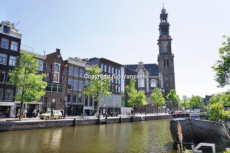 Nederland, Amsterdam, 7-5-2020 De regering laat het normale dagelijks leven weer langzaam opstarten . Door de afwezigheid van toeristen is het ongewoon rustig op de wallen en de rest van de binnenstad van Amsterdam en is de stad te zien zoals die pakweg voor de eeuwwisseling was . Een enkele toerist loopt met een rolkoffer op straat .   typisch,amsterdams,iconisch,historische,bebouwing,architectuur .  Unlock,beperkende,beperkingen, opheffen,versoepelen,versoepeling , opengooien, massatoerisme,toeristisch, toeristische,  Foto: Flip Franssen