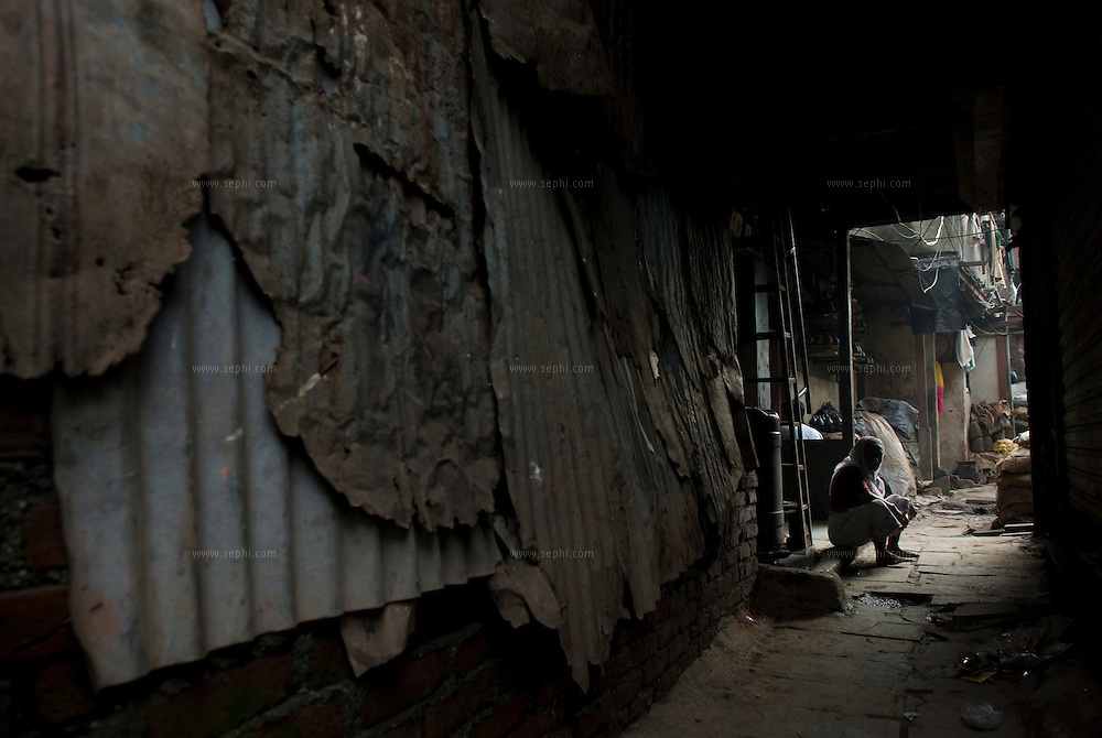 An old woman hunched outside her home of corrugated mettal in Dharavi's Kumbharwada.