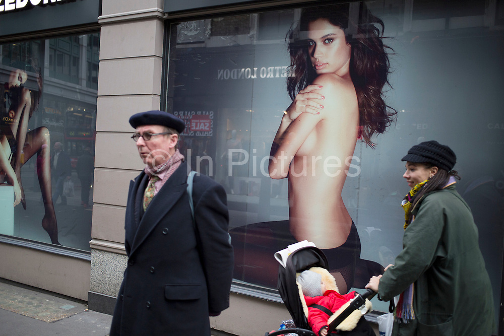 Street scene on Oxford Street, London, UK. Passers by interact with a large scale advertising picture for a lingerie company depicting a semi clad model looking out to the shoppers below, to entice them in.