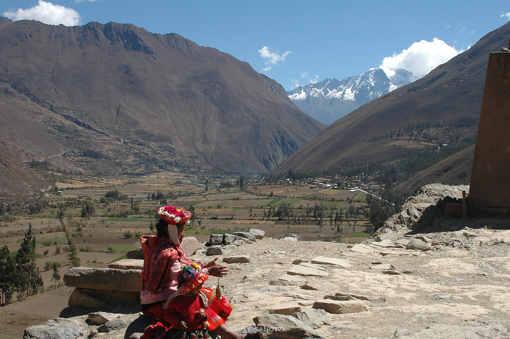 Inca Woman in Native Costume weaving in Ollantaytambo with a view of the Andes in the background.
