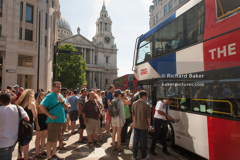 A tour bus with The Original Tour picks up passengers with St. Paul's Cathedral beyond, on Ludgate Hill, on 7th July 2017, in central London.