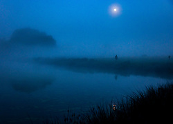 © Licensed to London News Pictures. 22/09/2021. London, UK. The full harvest moon sets over a misty Pen Ponds in Richmond Park the first day of autumn. Warm temperatures have heralded the start of the autumn season this week. Photo credit: Peter Macdiarmid/LNP