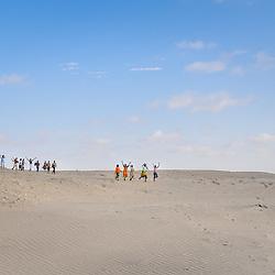 Um grupo de mulheres a atravesar as dunas do deserto do Namibe, a cantar e a dançar. Província do Namibe, Angola