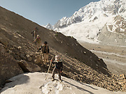A young trekker leads the way on a trek in the Hindukush.<br /> Trekking over the Darkot pass (4690m), linking Darkor village (Yasin Valley) to Chikar, below Boroghil pass on the Afghanistan border.