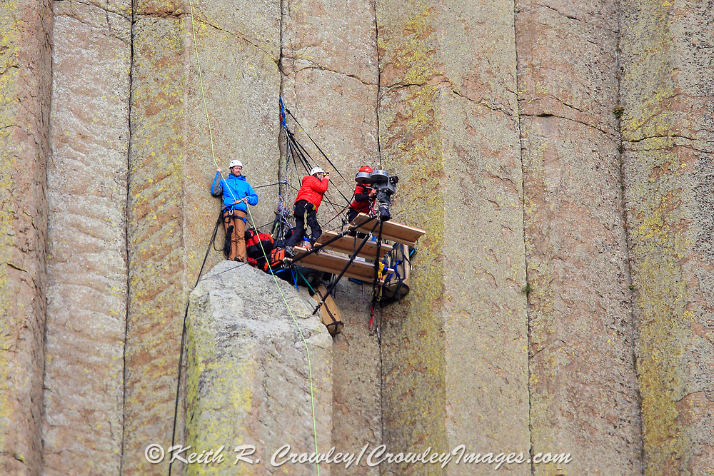 A film crew shoots an IMAX movie from a platform secured to Devils Tower
